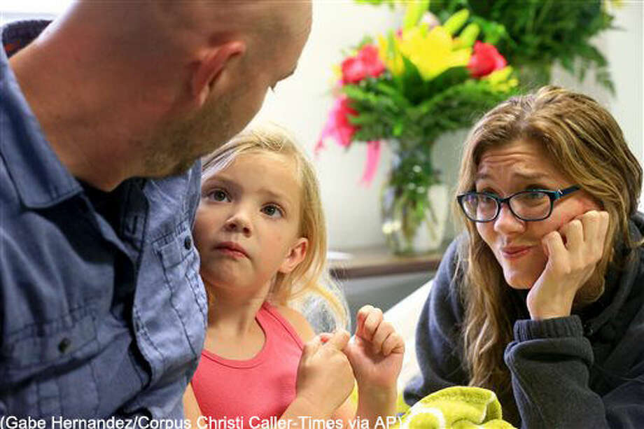 Allison Anderwald, 5, center, sits with her father, Ryan and her mother Tracy at Christus Spohn Hospital Memorial on Tuesday, March 22, 2016 in Corpus Christi, Texas. Allison saved her mother after she fell unconscious in their swimming pool . (Gabe Hernandez/Corpus Christi Caller-Times via AP) MANDATORY CREDIT; MAGS OUT; TV OUT Photo: Gabe Hernandez