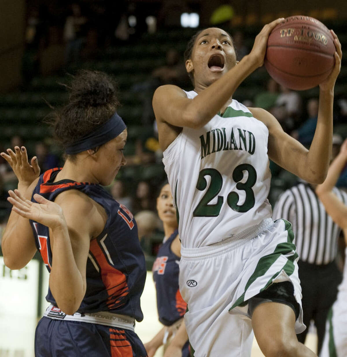 Midland College's Mary Savoy drives in for a lay up as South Plains' Jasmine Brainard gets out of the way Monday evenig at the Chaparral Center. Tim Fischer\Reporter-Telegram