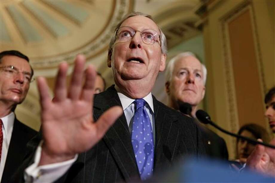 Senate Minority Leader Mitch McConnell, R-Ky., joined by, from left, Sen. John Barrasso, R-Wyo., and right by Senate Minority Whip John Cornyn, R-Texas, speaks to reporters following a closed-door Republican policy meeting, at the Capitol in Washington, Tuesday, Feb. 25, 2014. Senator McConnell says he sees no hope for enactment of tax overhaul legislation this year, and blames the Democrats for trying to use the issue to raise revenue by $1 trillion. The Kentucky Republican said the object of overhauling the tax code should be making the nation more competitive, not raising more money for the government. (AP Photo/J. Scott Applewhite) Photo: J. Scott Applewhite / AP