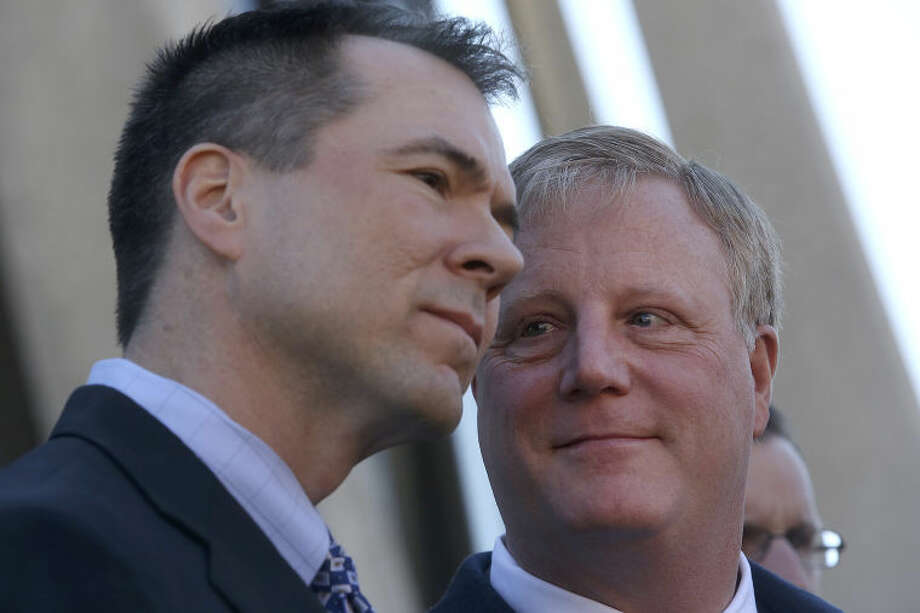Mark Phariss, right, looks at his partner, Victor Holmes, as they stand behind their attorneys as they speak to the media after the hearing for their request for a preliminary injunction to declare Texas' ban on same-sex marriage unconstitutional at the John H. Wood, Jr. U.S. Courthouse in San Antonio on Wednesday, Feb. 12, 2014. Photo: LISA KRANTZ