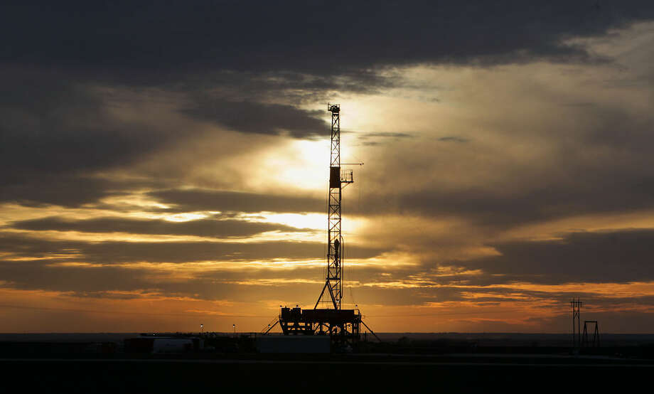 This Feb. 17, 2014 photo shows a rig in Howard county, Texas as the sun sets.