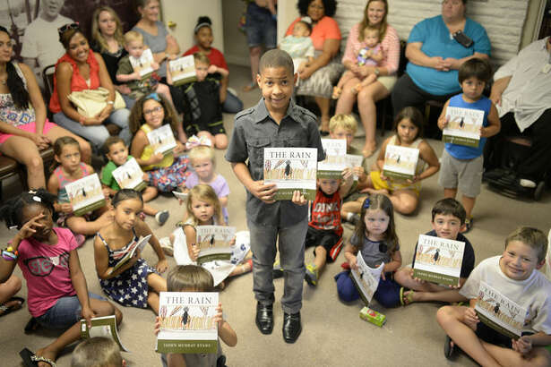 "Ten-year-old Jaden Evans poses for a photo after reading a book he wrote titled ""The Rain"" during a monthly reading event at the Bush Childhood Home on Thursday, July 16, 2015. James Durbin/Reporter-Telegram"