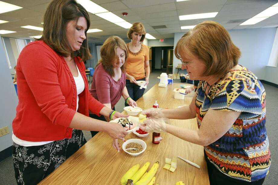 "(2012 File Photo) Cassie Emanuel, left, waits for Kay Crites, Big Brothers Big Sisters Executive Director, to top her ice-cream off with a banana Monday during a ""Banana Split Apeel"" at the MISD Administration building. Crites served ice-cream and met with administration building employees to talk to them about volunteering for the school based program which gives MISD employees one paid hour a week to mentor a child participating in BBBS. The employees will be allowed to leave the administration building to go to Crockett, Milam, Travis, or Sam Houston to spend the hour playing games, talking, or reading a book with their ""Little Brother"" or ""Sister."" All children who participated in the program last year showed an increase in self-confidence and 92 percent performed better in school. Cindeka Nealy/Reporter-Telegram Photo: Cindeka Nealy"