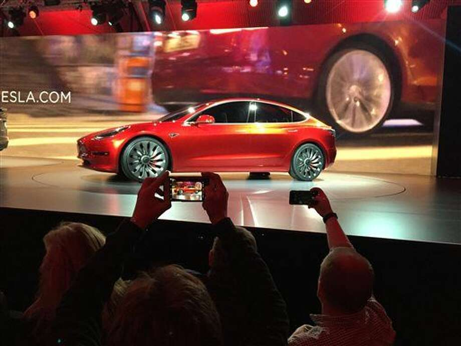 Tesla Motors unveils the new lower-priced Model 3 sedan at the Tesla Motors design studio Thursday, March 31, 2016, in Hawthorne, Calif. It doesn't go on sale until late 2017, but in the first 24 hours that order banks were open, Tesla said it had more than 115,000 reservations. Long lines at Tesla stores, reminiscent of the crowds at Apple stores for early models of the iPhone, were reported from Hong Kong to Austin, Texas, to Washington, D.C. Buyers put down a $1,000 deposit to reserve the car. (AP Photo/Justin Prichard) Photo: Justin Prichard
