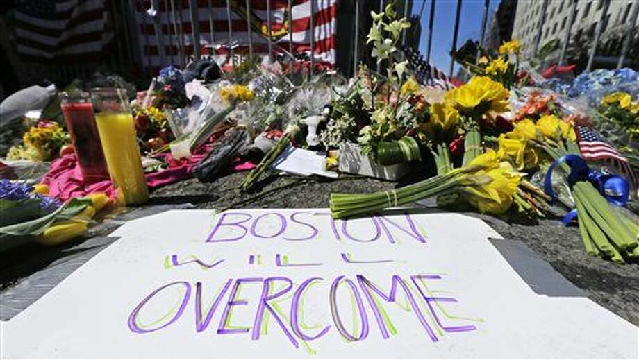 FILE - In this April 17, 2013 photograph, flowers and signs adorn a barrier, two days after two explosions killed three and injured hundreds, at Boylston Street near the of finish line of the Boston Marathon at a makeshift memorial for victims and survivors of the bombing. Boston will mark the second anniversary of the 2013 marathon bombings Wednesday, April 15, 2015 with a subdued remembrance that includes a moment of silence, the pealing of church bells and a call for kindness. (AP Photo/Charles Krupa, File) Photo: Charles Krupa