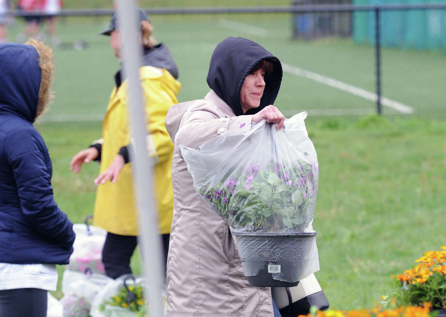 "Deb Gambino of Greenwich buys a hanging flower plant during the Greenwich High School Softball Program's Mother's Day Plant sale at the school in Greenwich, Conn., Friday afternoon, May 6, 2016. Carolyn Decker, a volunteer who was one of the people selling plants, said that most of the volunteers are parents of students involved in the freshmen, junior varisty or varsity Greenwich High School softball program. Decker said ""It is our big fund raiser and we will be here all day Saturday at Greenwich High School, 9 a.m. to 5 p.m, so please come by and get your Mother's Day plants from us. We will make you a hero.""  Sue Delepine, another volunteer helping out said "" We have all kinds of plants, vegetables, tomatoes, potted plants and all kinds of flowers. All the money raised from the sale goes to support the GHS softball program and to provide new equipment."" Photo: Bob Luckey Jr. / Hearst Connecticut Media / Greenwich Time"