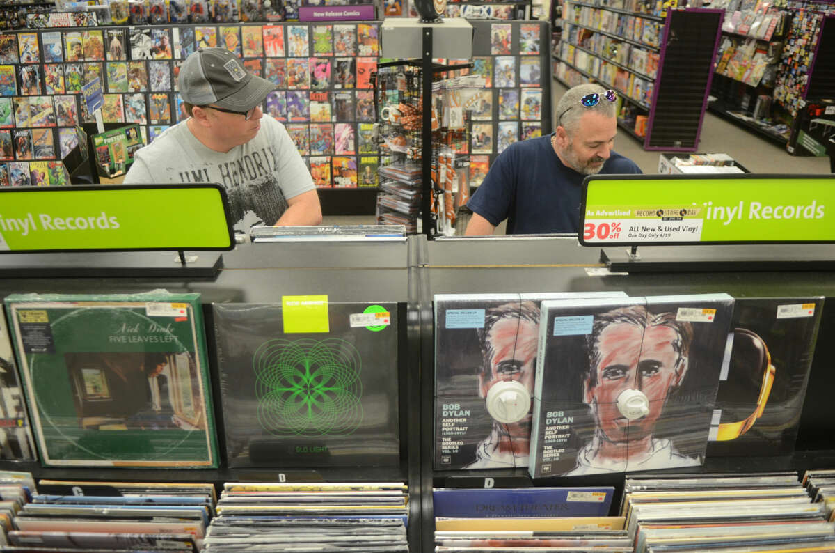 Matt Walsh of Midland, left, and Tony Priest of Crane, right, peruse vinyl records at Hasting's during National Record Store Day on Saturday. James Durbin/Reporter-Telegram
