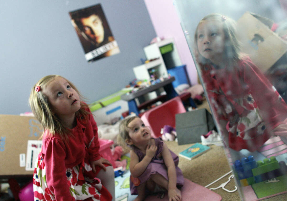 FILE - In this Monday, Feb. 25, 2013 file photo, with her face reflected in a mirror, Coy Mathis, left, a transgender girl, plays with her sister, Auri, 2, center, at their home in Fountain, Colo.