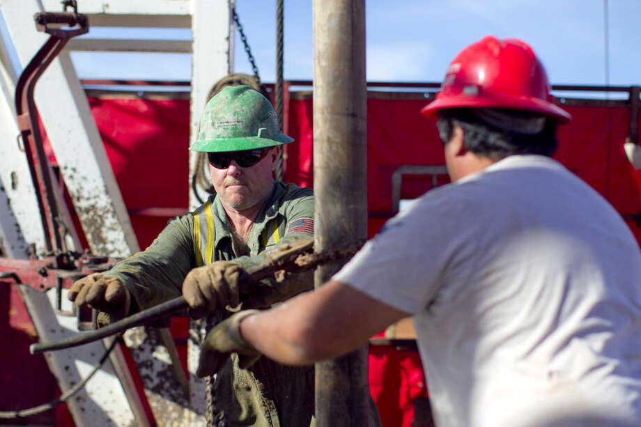 Guy Cummings (left) and Desiderio Castillo (right) work to assemble a 90-foot section of pipe on the drilling floor of Robinson Drilling rig #4 on Wednesday, Feb. 17, 2016, in Midland County. James Durbin/Reporter-Telegram