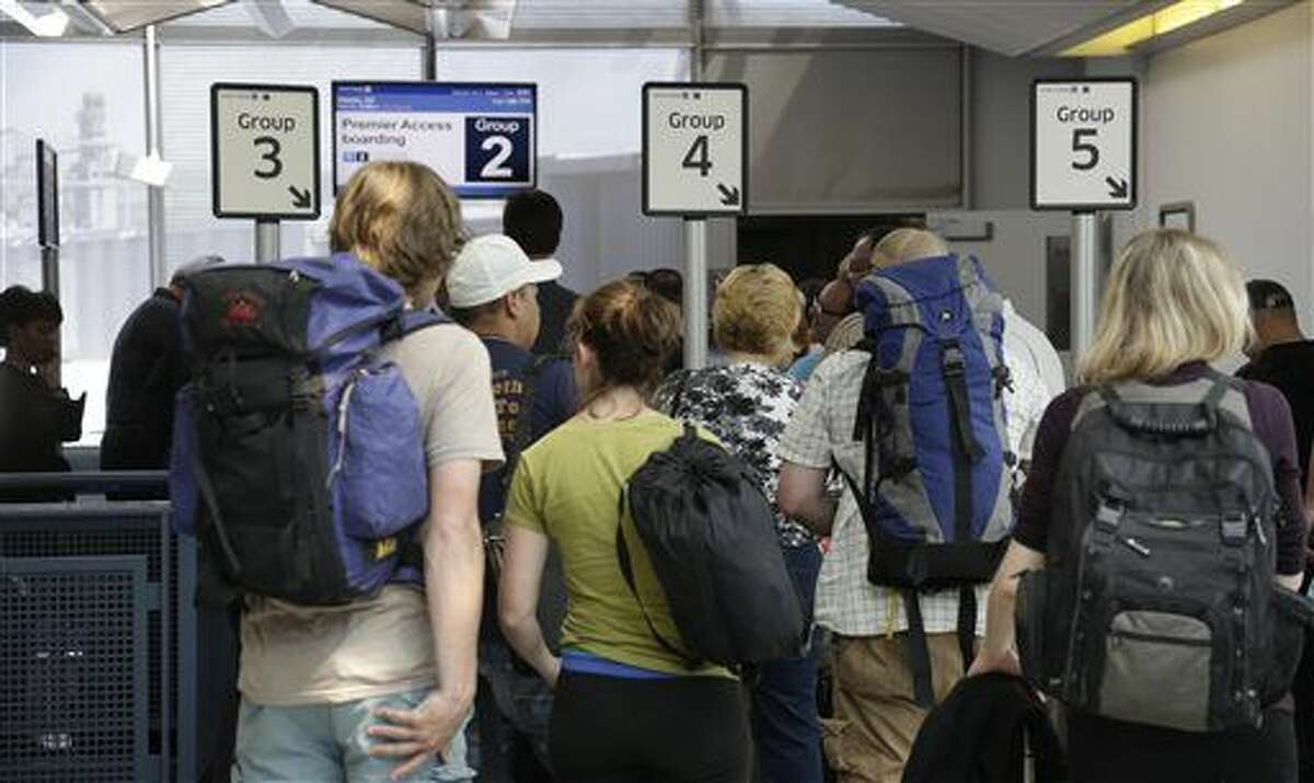 FILE - In this file photo taken May 8, 2013, groups of passengers wait at a United Airlines gate to board a flight in separate numbered lanes at O'Hare International Airport in Chicago. Planes are filled with more passengers than ever before, fliers are older and heavier and tall travelers no longer get exit row seats for free. All of this, flight attendants warn, is leading to an increased amount of air rage. Just last summer two passengers got into a mid-air fight over reclining a seat. (AP Photo/M. Spencer Green)