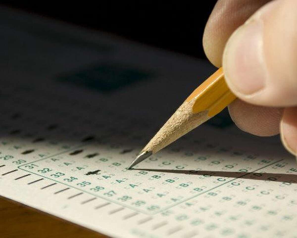 Extreme closeup in dramatic lightingofchild's hand marking standardized test form.