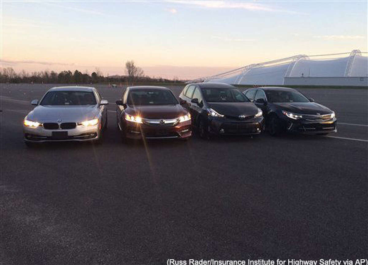 EMBARGOED UNTIL 12:01 A.M., WEDNESDAY, MARCH 30, 2016 - In this photo provided by the The Insurance Institute for Highway Safety, from left, a BMW 3 series, Honda Accord, Toyota Prius V and a Kia Optima are seen at the institute's Vehicle Research Center in Ruckersville, Va. A new study that rates the headlights of more than 30 midsized car models found only one model earned a