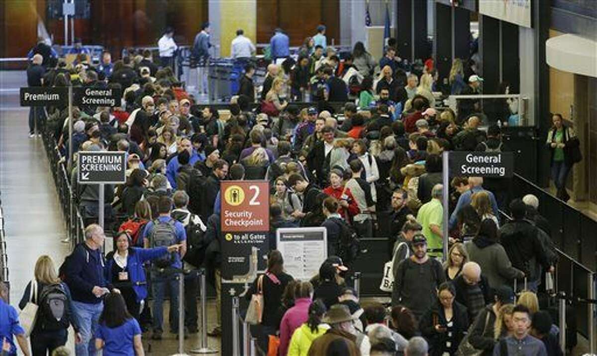 ADVANCE FOR RELEASE WEDNESDAY, MARCH 30, AND THEREAFTER - In this March 17, 2016, photo, travelers wait in line for security screening at Seattle-Tacoma International Airport in Seattle. Fliers will likely face massive security lines at airports across the country this summer, with airlines already warning passengers to arrive at least two hours early or risk missing their flight. (AP Photo/Ted S. Warren)