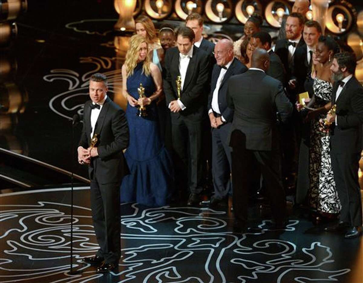 """Brad Pitt, left, speaks as he and the cast and crew of """"12 Years a Slave"""" accept the award for the best picture during the Oscars at the Dolby Theatre on Sunday, March 2, 2014, in Los Angeles. (Photo by John Shearer/Invision/AP)"""