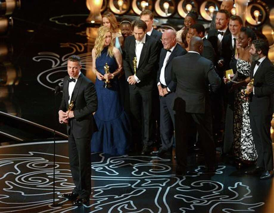 "Brad Pitt, left, speaks as he and the cast and crew of ""12 Years a Slave"" accept the award for the best picture during the Oscars at the Dolby Theatre on Sunday, March 2, 2014, in Los Angeles. (Photo by John Shearer/Invision/AP) Photo: John Shearer / Invision"