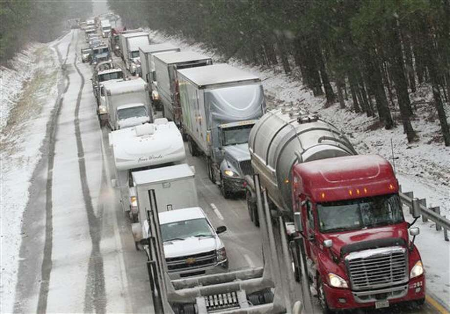 Motorists are at a standstill as emergency responders cleaned up a tractor-trailer wreck on Interstate 85 southbound near the Dinwiddie, Va. exit Monday, March 3, 2014. Winter kept its icy hold on much of the country Monday, with snow falling and temperatures dropping as schools and offices closed and people from the South and Mid-Atlantic to Northeast reluctantly waited out another storm indoors. (AP Photo/The Progress-Index, Patrick Kane) Photo: Patrick Kane / The Progress-Index