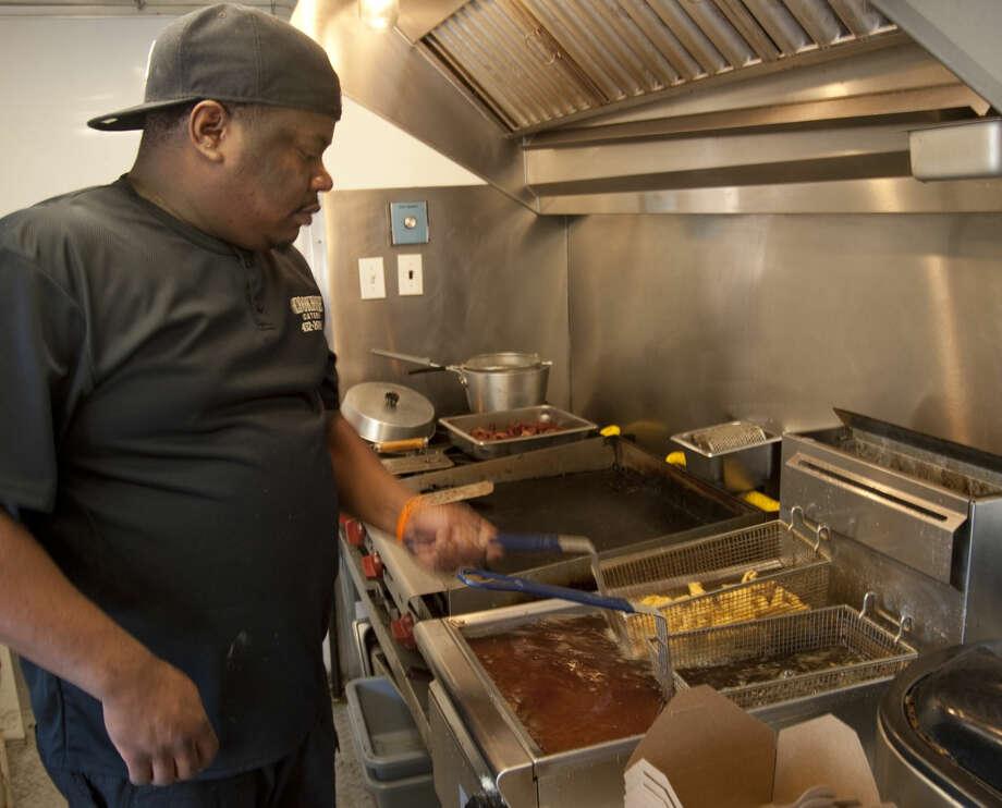 Samuel Ransom Jr. checks the fries Thursday, 3-12-15, as he preps orders in Cookhouse Catering food truck. Tim Fischer\Reporter-Telegram Photo: Tim Fischer