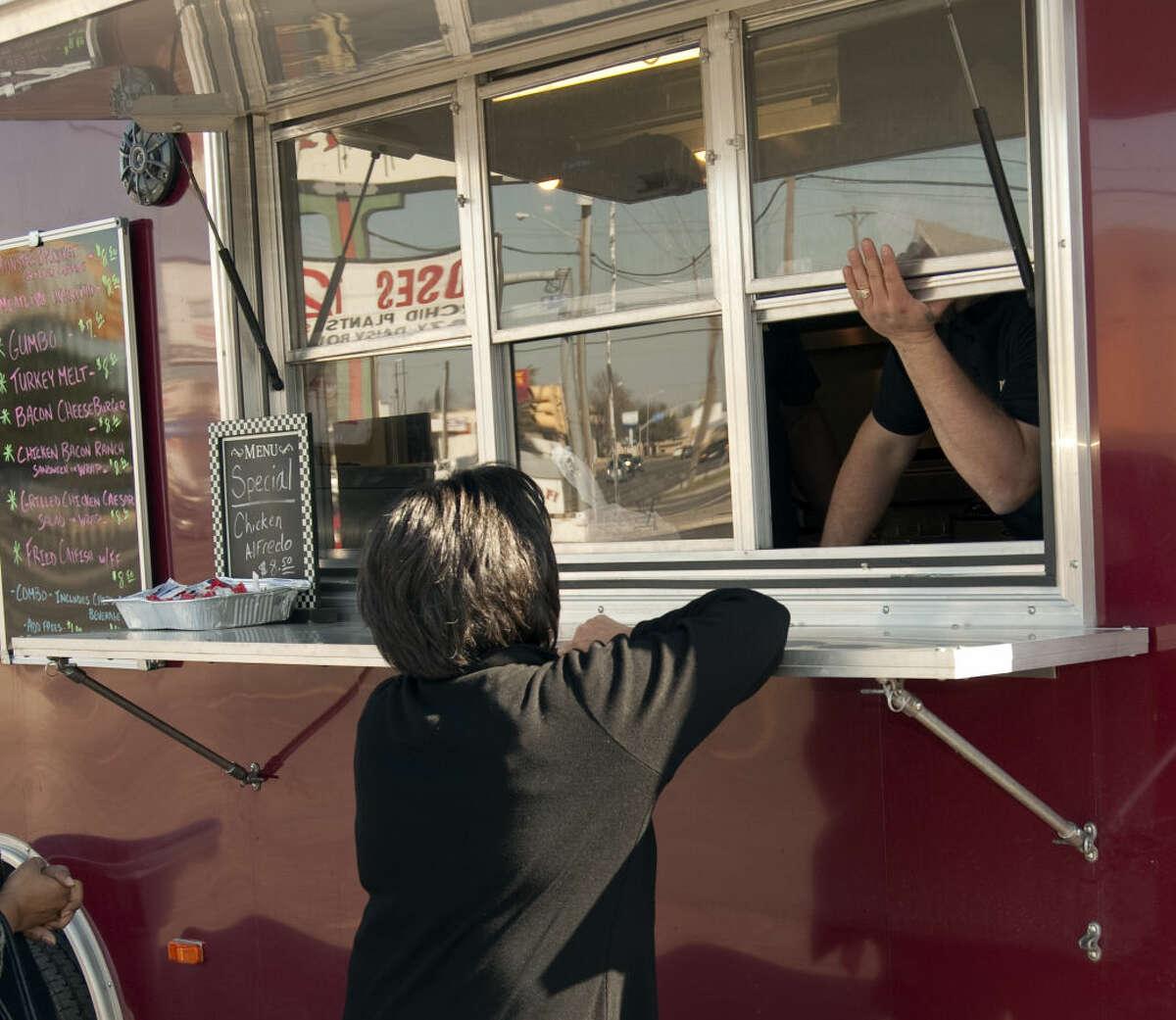 Yolanda Roberson puts her order in to Daniel Jimenez Thursday, 3-12-15, at Cookhouse Catering food truck. Tim Fischer\Reporter-Telegram