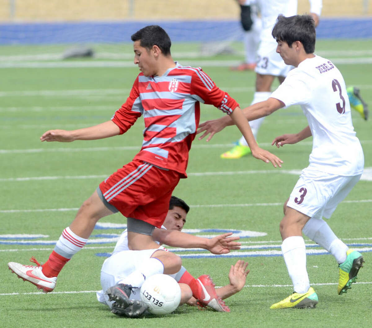 Lee's Cesar Gonzales slides into Odessa High's Jonathan Alvarez to knock the ball away Saturday at Grande Communications Stadium. Also pictured, Lee's Nathan Ortiz (3). James Durbin/Reporter-Telegram