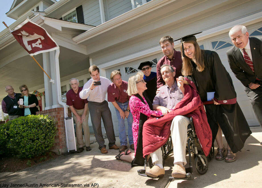 "Jim Brewer, center, sings ""The Sprit of Aggieland"" during the graduation ceremony for his daughter Jenny Brewer, right, from Texas A&M at his home in Circle C Ranch Tuesday March 22, 2016 in Austin. Brewer, 57, is nearing the end of his struggle with pancreatic cancer, watched his daughter graduate from Texas A&M University,his alma mater. Doctors said Brewer's time is short, Texas A&M brought the ceremony to his home as dozens of relatives, neighbors and friends looked on, many wearing Aggie maroon. (Jay Janner/Austin American-Statesman via AP) AUSTIN CHRONICLE OUT, COMMUNITY IMPACT OUT, INTERNET AND TV MUST CREDIT PHOTOGRAPHER AND STATESMAN.COM, MAGS OUT; MANDATORY CREDIT"