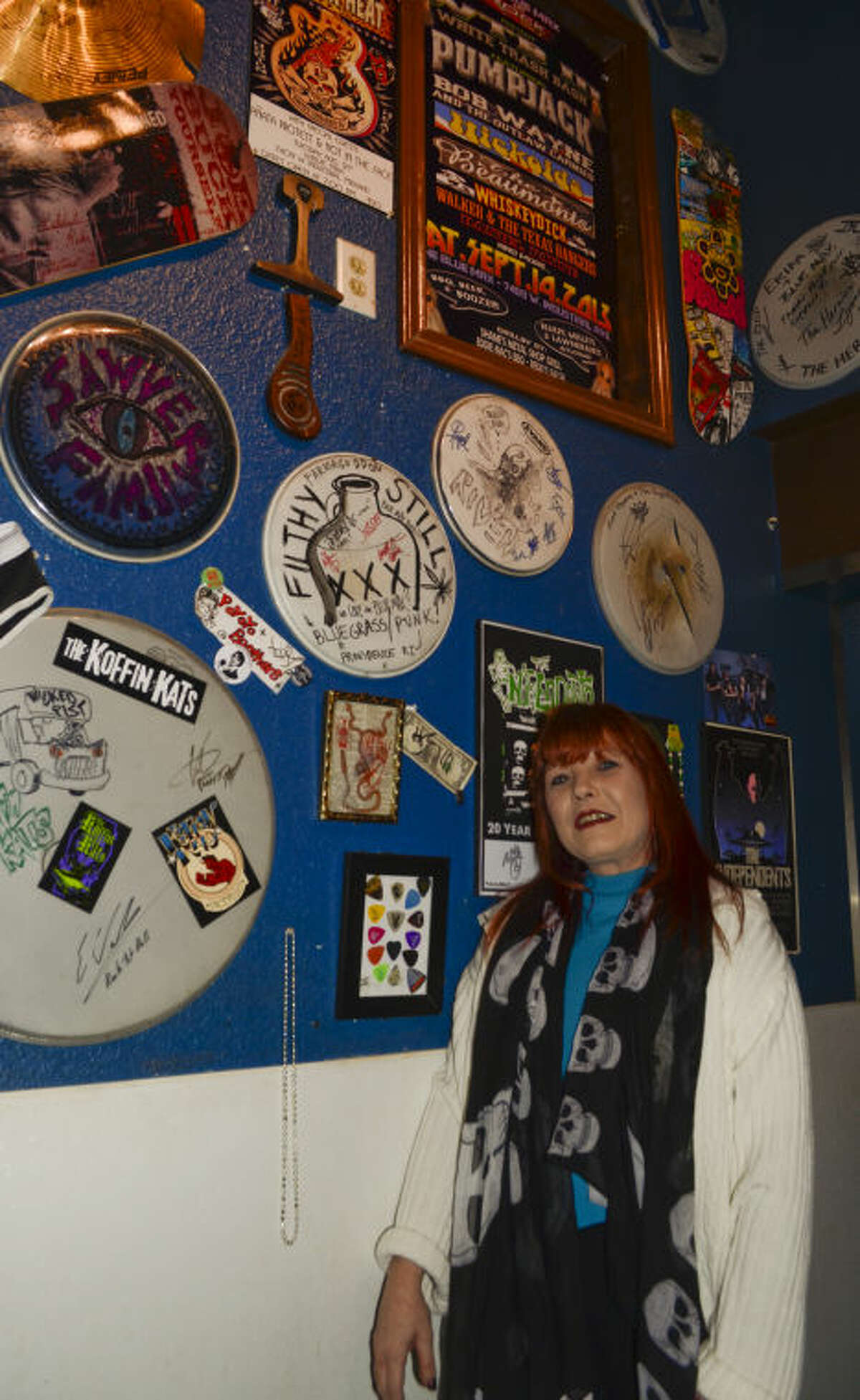 Erika Berry, owner of the Blue Max, stands next to a wall with mementoes from some of the bands that have played at the bar. Tim Fischer\Reporter-Telegram