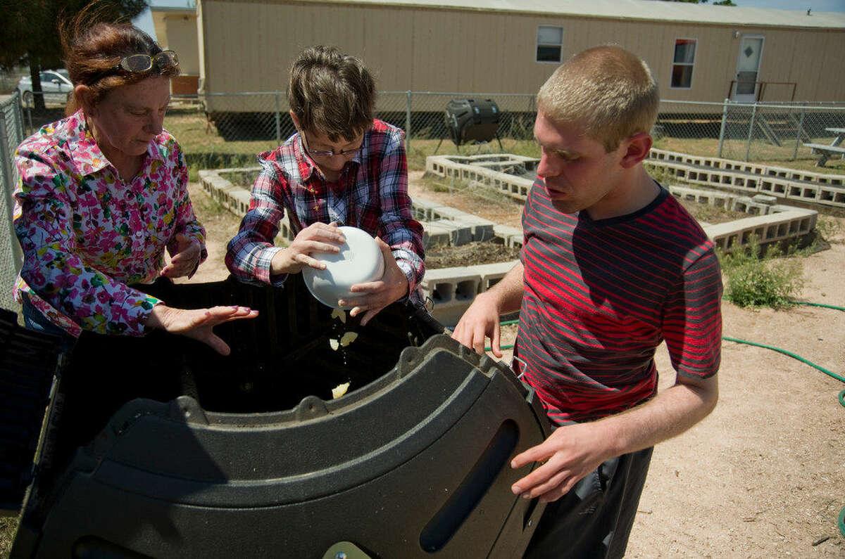 inda Miller supervises as Kara Claxton and Sam Neiman put food scraps into the composting bin Monday 03-28-16 in the garden atBynumSchool. Tim Fischer\Reporter-Telegram