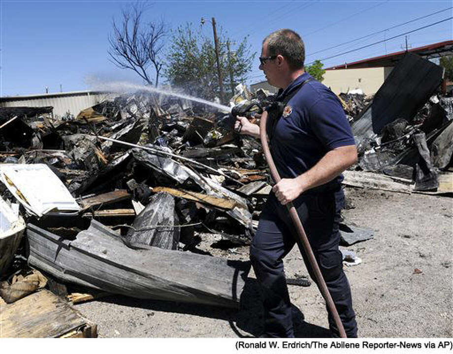 In this Sunday April 3, 2016 photo, Zach Williams of the Abilene Fire Department Station 2 waters down the remains of the Christian Service Center in Abilene, Texas. The facility which supplied clothing, food and household items to those in need, burned to the ground Saturday. (Ronald W. Erdrich/The Abilene Reporter-News via AP) MANDATORY CREDIT Photo: Ronald W. Erdrich