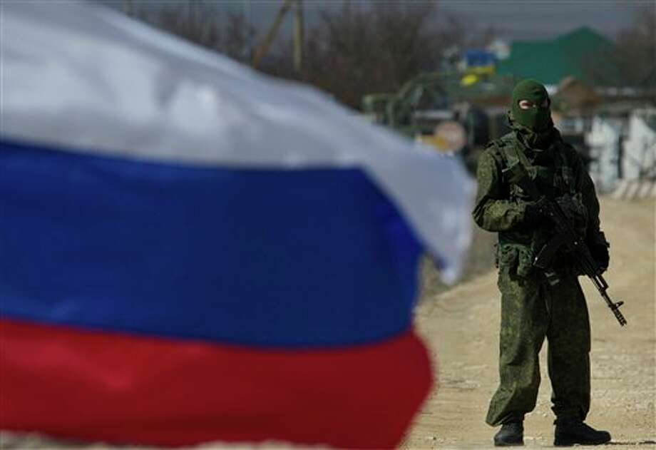 Pro-Russian soldiers block the Ukrainian naval base in the village of Novoozerne, some 91 km west of Crimean capital Simferopol, Ukraine, on Monday, March 3, 2014. Ukraine says Russian forces controlling the strategic region of Crimea are demanding that the crew of two Ukrainian warships in Sevastopol's harbor must surrender. (AP Photo/Ivan Sekretarev) Photo: Ivan Sekretarev / AP