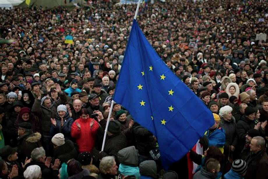 "People applaud as the European Union flag held by a protester arrives at the Independence square during a rally in Kiev Ukraine, Sunday, March 2, 2014. Ukraine's new prime minister urged Russian President Vladimir Putin to pull back his military Sunday in the conflict between the two countries, warning that ""we are on the brink of disaster."" The comments from Arseniy Yatsenyuk came as a convoy of Russian troops rolled toward Simferopol, the capital of Ukraine's Crimea region, a day after Russian forces took over the strategic Black Sea peninsula without firing a shot. (AP Photo/Emilio Morenatti) Photo: Emilio Morenatti / AP2014"