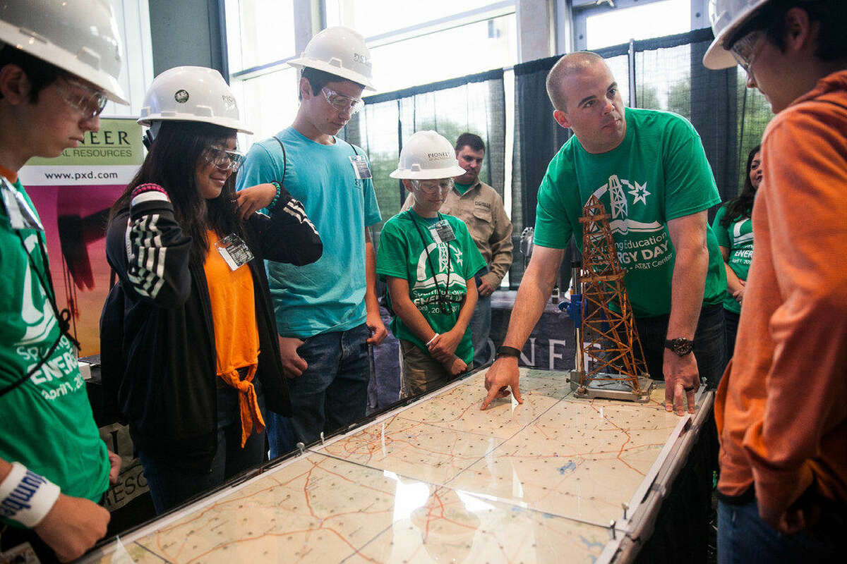Pioneer Natural Resources Engineer Erik Gragg shows students where they will drill oil from Friday April 1, 2015 during theSpurringEducation Energy Day hosted by The Eagle Ford Shale industry group South Texas Energy & Economic Roundtable at the AT&T Center. Booths and hands-on activities were available to middle school and high school students from San Antonio and throughout South Texas with interest in STEM, oil or gas industry careers. Companies offering educational opportunities to students at theSpurringEducation Energy Day include: Anadarko, ConocoPhillips, EOG, Halliburton, Howard Energy, Marathon Oil, Noble Energy, Pioneer Natural Resources, Schlumberger and Statoil.