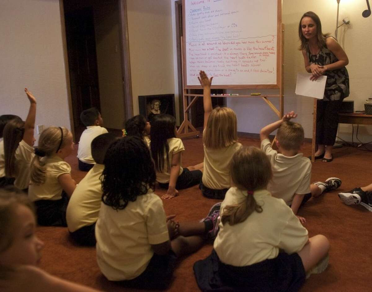 Katy Gillan, a music teacher at St. Ann's, talks to first grade students in this 2011 file photo. A Catholic private school appears headed to the Permian Basin.