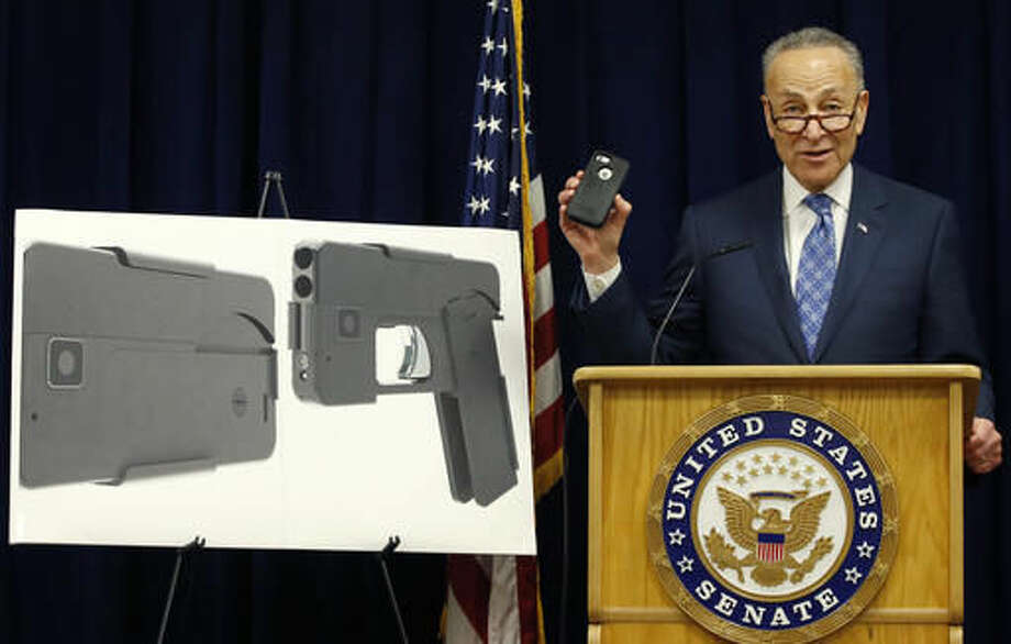 Standing beside photographs of a new product, U.S. Sen Charles Schumer, (D-New York), shown holding an iPhone 5S, voices his opposition to a handgun that appears to be a cell phone during a news conference in his office, Monday, April 4, 2016, in New York. According to the website of Ideal Conceal, the company has developed a double-barreled, .380 caliber handgun that can serve as a concealed weapon. The gun lists for $395. (AP Photo/Kathy Willens) Photo: Kathy Willens