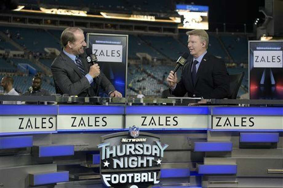 "FILE - In this Nov. 19, 2015, file photo, Thursday Night Football sportscasters Bill Cowher, left, and Phil Simms broadcast from the set on the field before an NFL football game between the Jacksonville Jaguars and the Tennessee Titans in Jacksonville, Fla. The NFL has picked Twitter to stream its Thursday night games. When the league negotiated its latest deal for Thursdays, it decided to sell the streaming rights separately for an ""over the top"" broadcast. (AP Photo/Phelan M. Ebenhack, File) Photo: Phelan M. Ebenhack"