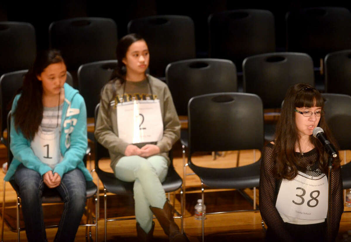 Nikkie Galindo of Trinity School spells during the Midland Reporter Telegram's 27th annual regional spelling bee Saturday at Midland College's Allison Fine Arts Building. The last remaining contestants are pictured in the background, Gloria Koo of Abell Junior High, left, and Gabrielle Rubio of Alamo Junior High, center. James Durbin/Reporter-Telegram