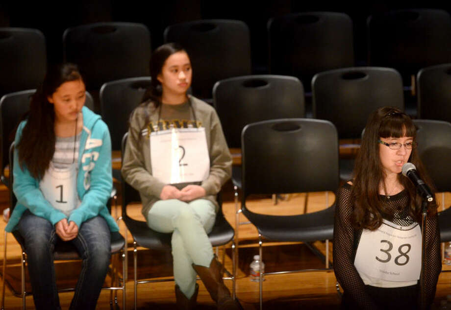 Nikkie Galindo of Trinity School spells during the Midland Reporter Telegram's 27th annual regional spelling bee Saturday at Midland College's Allison Fine Arts Building. The last remaining contestants are pictured in the background, Gloria Koo of Abell Junior High, left, and Gabrielle Rubio of Alamo Junior High, center. James Durbin/Reporter-Telegram Photo: JAMES DURBIN
