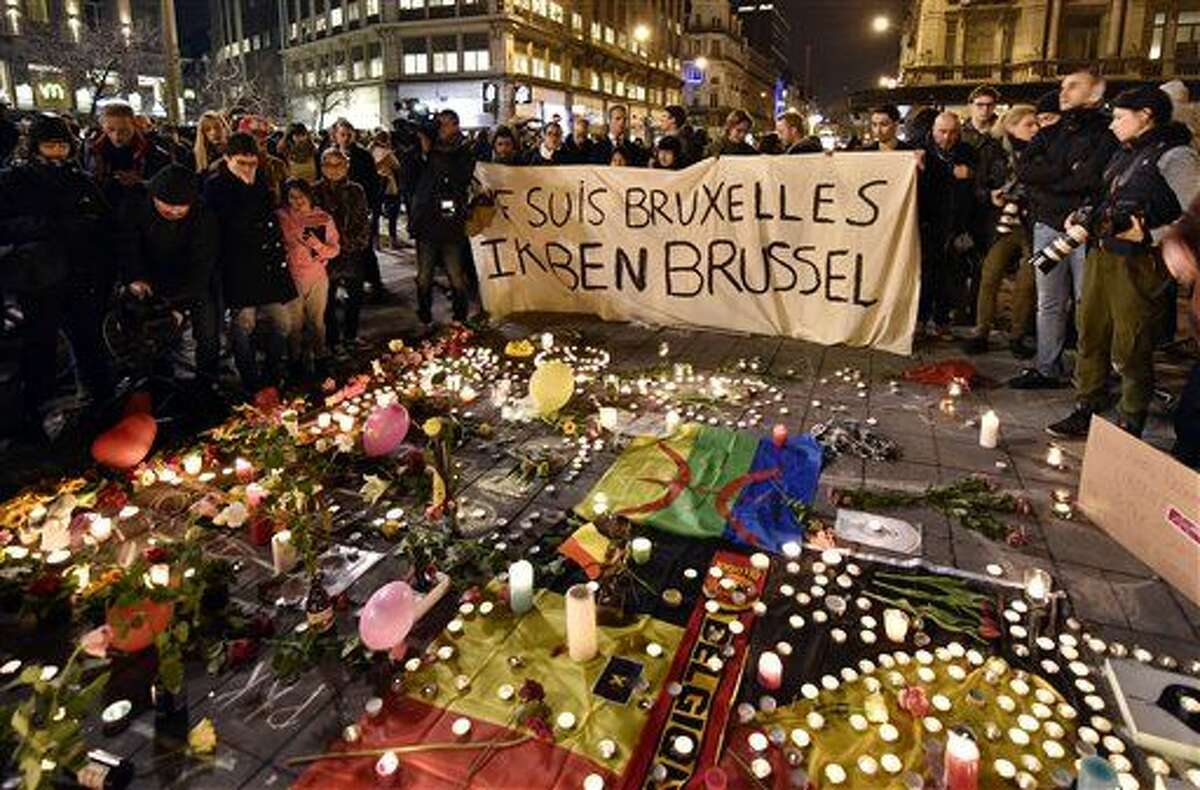 """People holding a banner reading """"I am Brussels"""" behind flowers and candles to mourn for the victims at Place de la Bourse in the center of Brussels, Tuesday, March 22, 2016. Bombs exploded at the Brussels airport and one of the city's metro stations Tuesday, killing and wounding scores of people, as a European capital was again locked down amid heightened security threats. (AP Photo/Martin Meissner)"""