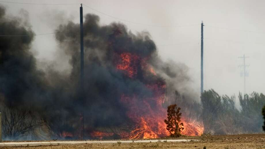Tall dry grasses and high winds made the fire difficult to contain as it spread east from FM 1788. Photo by Tim Fischer/Midland Reporter-Telegram Photo: Tim Fischer