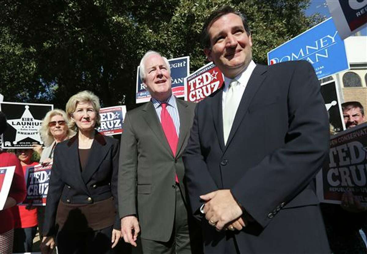 File - In this Nov. 1, 2012 file photo, then Republican candidate for U.S. Senate Ted Cruz, right, U.S. Senators Kay Bailey Hutchison, left, and John Cornyn listen to a question from reporters outside a polling station in Dallas. Cruz refused to endorse his colleague Cornyn before the 2014 Texas primary. But a resounding Cornyn victory has changed Cruz's mind. (AP Photo/LM Otero, File)