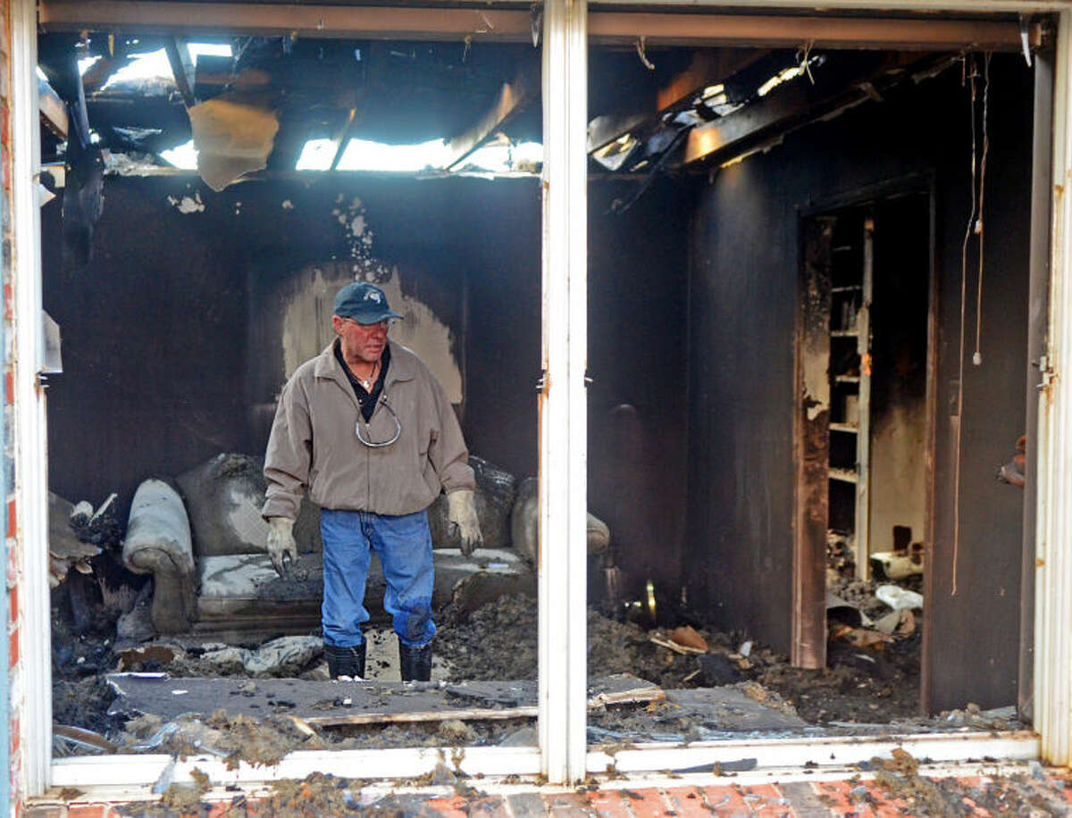 """Scott Baggett picks through the remains of his burned house on Seaboard Ave. on Wednesday. Baggett says he lost everything in the fire, including his dog Bubba Jack. """"I have great friends and family,"""" said Baggett, """"I will be ok."""" James Durbin/Reporter-Telegram"""