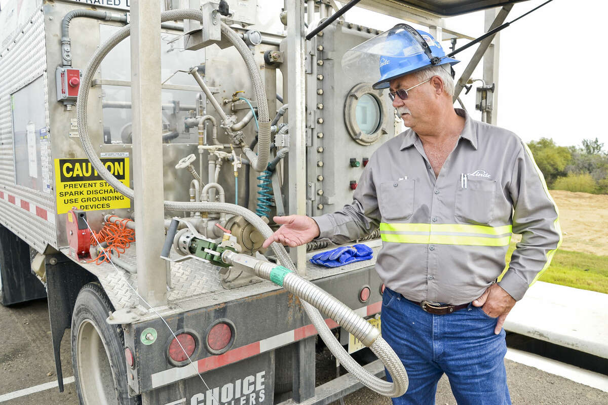 Linde truck driver, Howard Sanford, stands next to a portable refueling station for vehicles that operate on natural gas as opposed to gasoline, Tuesday afternoon outside of Uni-Trade Stadium during the South Central Texas Natural Gas Vehicle Consortium Meeting.