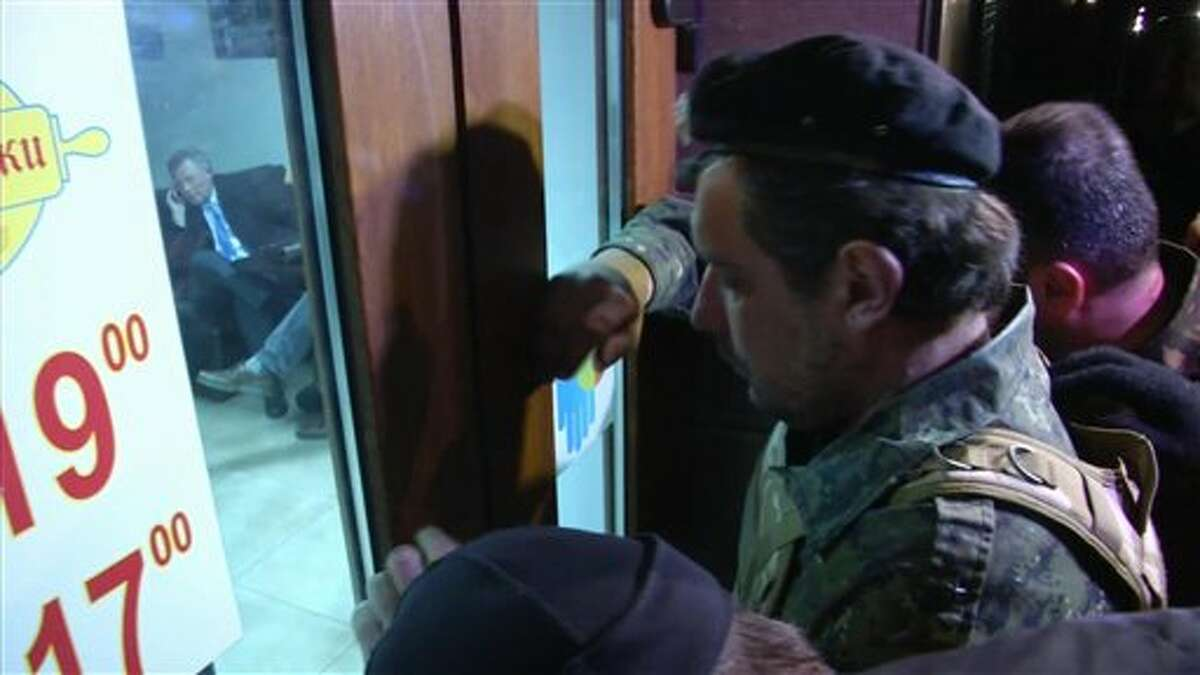 """This image taken from AP video shows a group of unidentified men in military fatigues outside a cafe in Simferopol, Ukraine who appear to be stopping UN Special Envoy to Ukraine, Robert Serry from leaving as he makes a call on his mobile phone inside, Wednesday, March 5, 2014. The special U.N. envoy who is visiting Crimea was threatened by 10 to 15 armed men on Wednesday and ordered to leave the region, where Ukraine and Russia are locked in a tense standoff, U.N. officials said. Later, an Associated Press reporter found Robert Serry in the business class lounge of the Simferopol airport on Wednesday evening. """"I'm safe. My visit was interrupted for reasons that I cannot understand,"""" the Dutch diplomat said in a statement to AP. He said nothing more. (AP Photo/AP video)"""