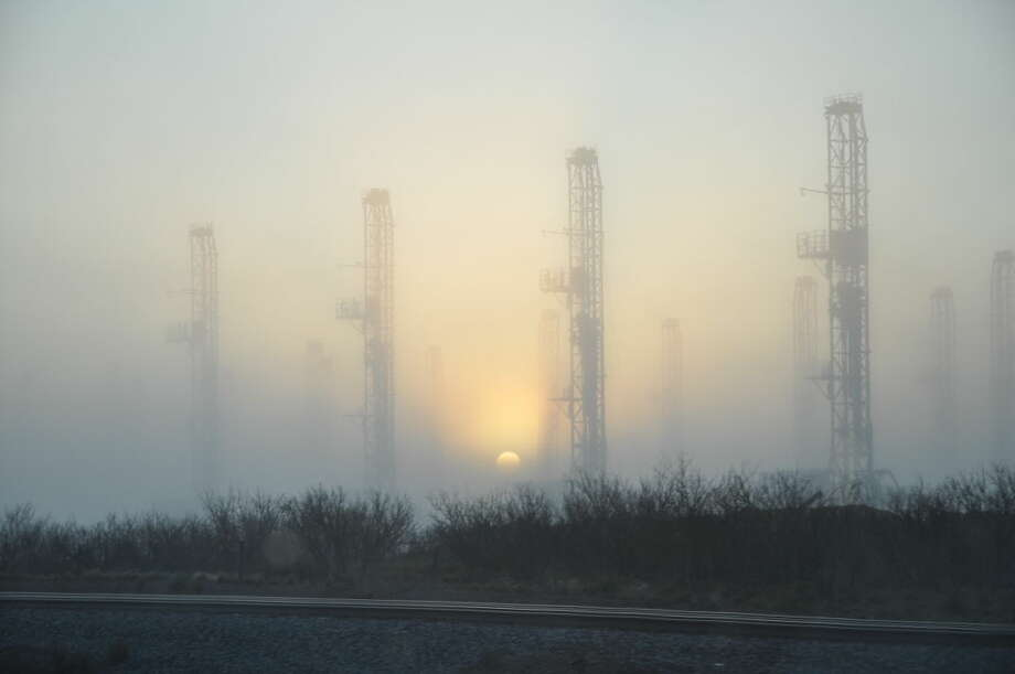 Drilling rigs along Business 20 are pictured in the fog near Odessa on March 10, 2015.  Photo: Rye Druzin/Reporter-Telegram