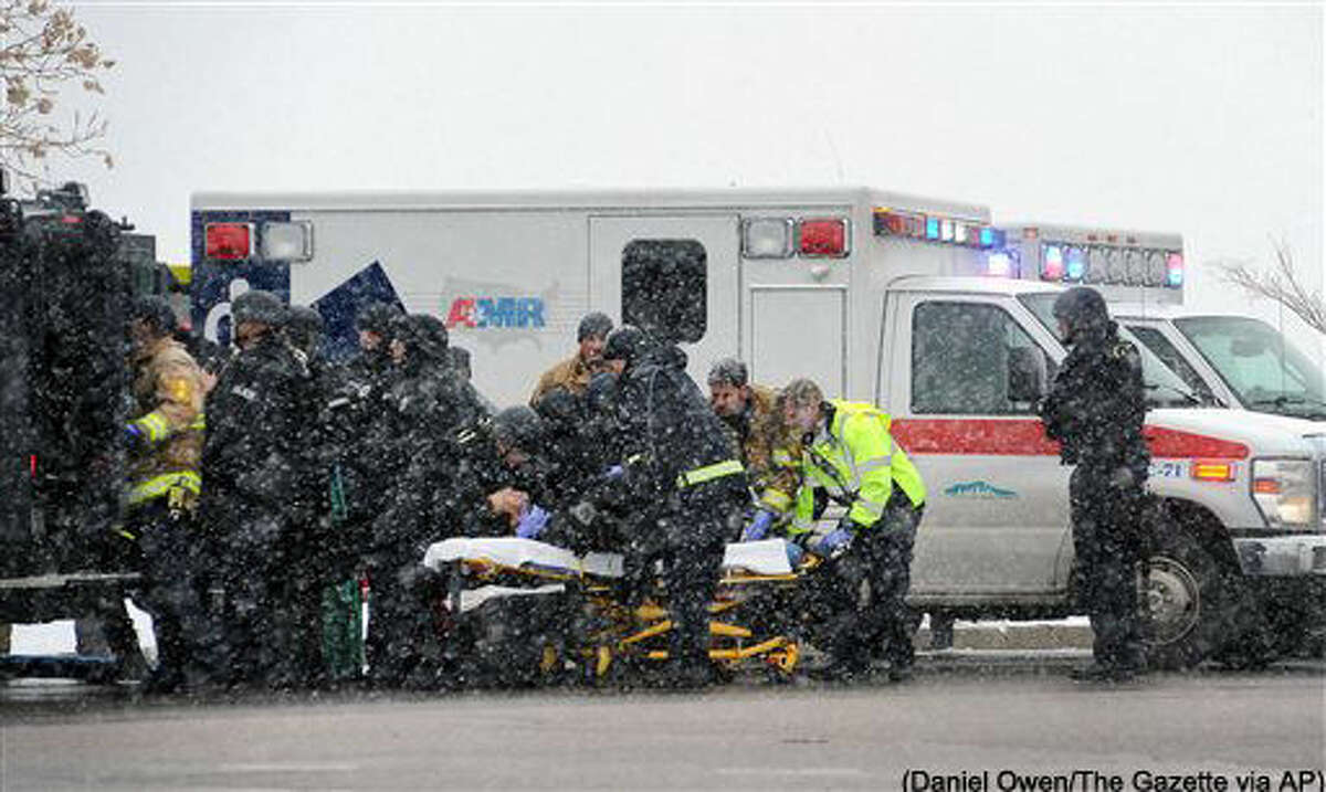 FILE - In this Nov. 27, 2015 file photo, emergency personnel transport an officer to an ambulance after reports of a shooting at the Planned Parenthood clinic in Colorado Springs, Colo. Threats and violence directed at U.S. abortion clinics increased sharply in 2015, according to the National Abortion Federation, which attributed the surge to the release of undercover videos intended to discredit Planned Parenthood. (Daniel Owen/The Gazette via AP, File) MAGS OUT; MANDATORY CREDIT