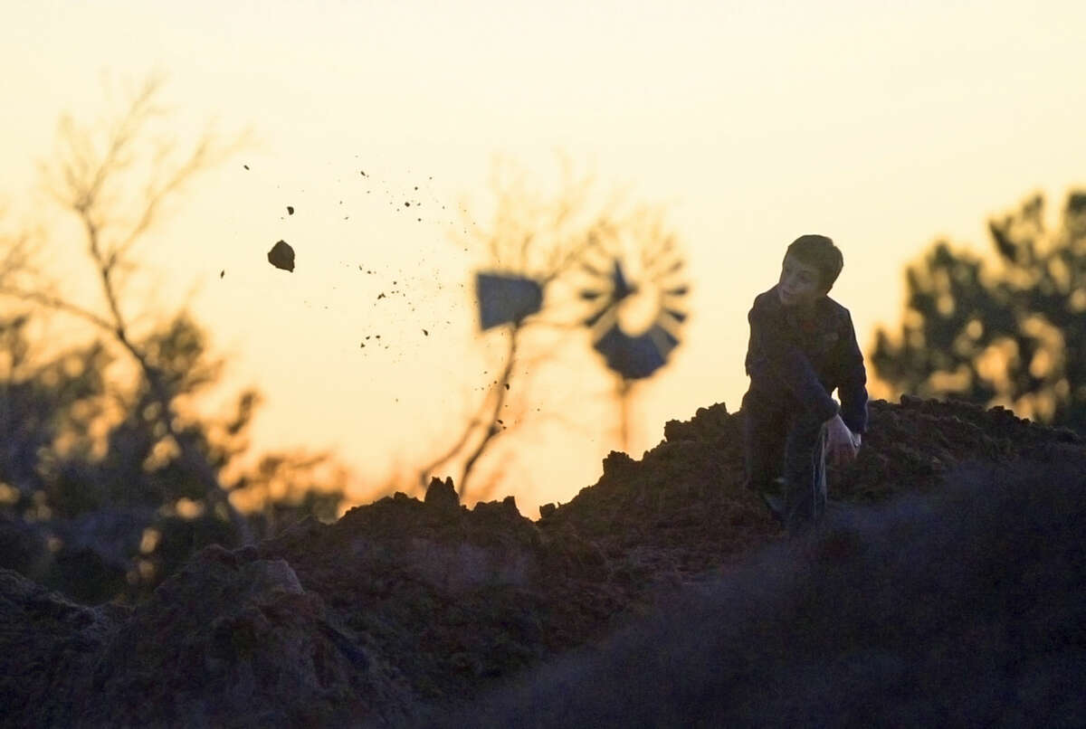 A young Midlander plays in a dirt pile as the sun sets over Midland Country Club before the start of the West Texas Sports Banquet on Wednesday, Feb. 3, 2016. James Durbin/Reporter-Telegram