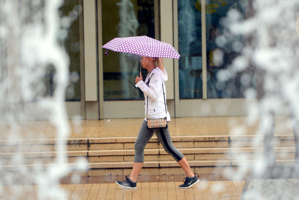 With her umbrella out, Texas A&M University sophomore Ashley Kirby of Katy passes by Rudder Fountain on Nov. 5 while on her way home from class in College Station. A cold front has dumped inches of rain on the Brazos Valley in early November and is expected to return this week.