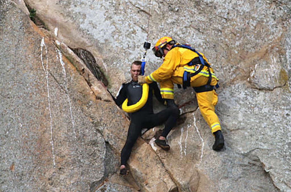 In this photo provided by Bob Isenberg, Michael Banks is stranded on a ledge some 80 feet off the ground on Morro Rock, a landmark in Morro Bay, Calif., Thursday, April 7, 2016. He had scaled the rock to make an Internet proposal to his girlfriend - who said yes - but then got stuck on a ledge and couldn't get down. A helicopter had to be called, and Morro Bay Fire Department Capt. Todd Gailey was lowered by cable to pluck Banks and take him to safety.(Bob Isenberg via AP)