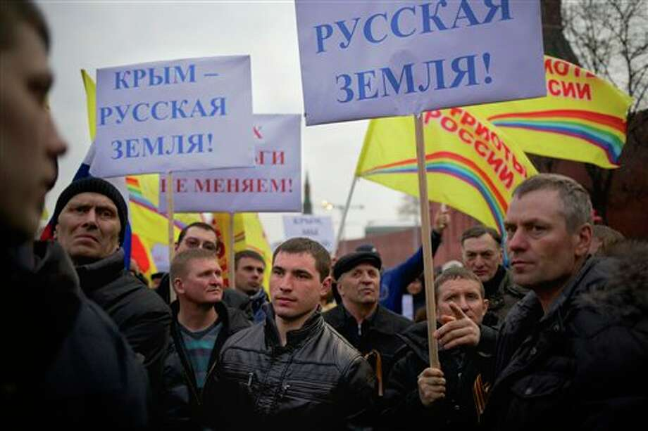 "Pro-Putin demonstrators hold posters reading ""Crimea is Russian land!"" as they gather towards to Red Square in Moscow, Russia, Friday, March 7, 2014. Russia rallied support Friday for a Crimean bid to secede from Ukraine, with a leader of Russia's parliament assuring her Crimean counterpart that the region would be welcomed as ""an absolutely equal subject of the Russian Federation."" Across Red Square, 65,000 people waved Russian flags, chanting ""Crimea is Russia!""(AP Photo/Alexander Zemlianichenko) Photo: Alexander Zemlianichenko / AP"