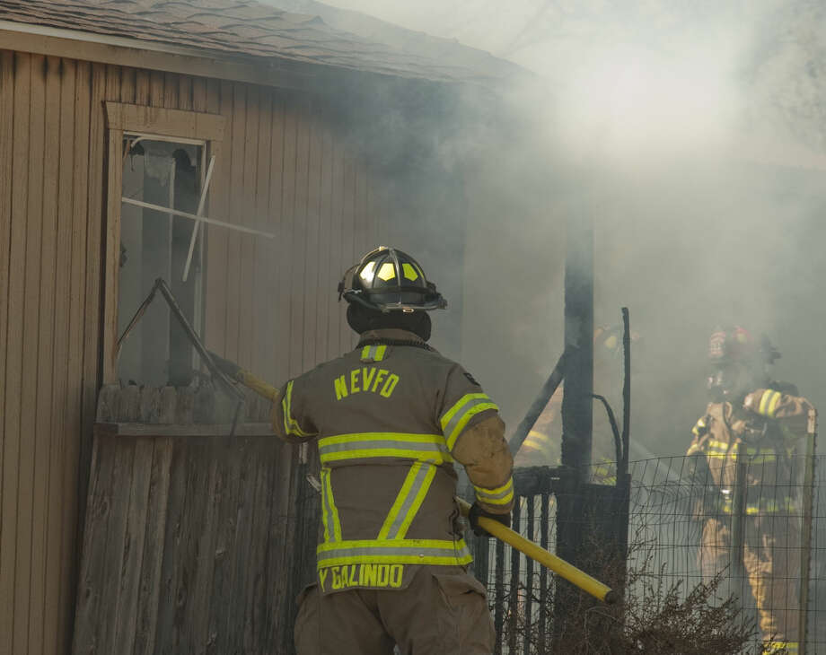 Midland firefighters with Northeast volunteer firefighters work to contain a fire in an unattached shed Monday, 2-2-15, before it spread to the mobile home right next to the building in the 2200 block of North County Road 1134. Tim Fischer\Reporter-Telegram Photo: Tim Fischer