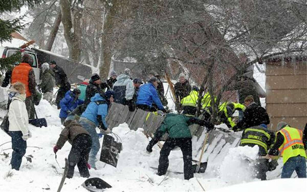 Rescuers dig frantically at the scene of an avalanche in Missoula's Rattlesnake Valley on Friday, Feb. 28, 2014, looking for a boy buried in the snow. The avalanche roared into a residential neighborhood and destroyed a house, but three people were found alive amid the snow and wreckage, police said. The survivors were an elderly couple and an 8-year-old boy, police Sgt. Travis Welsh said. (AP Photo/The Missoulian, Tom Bauer)