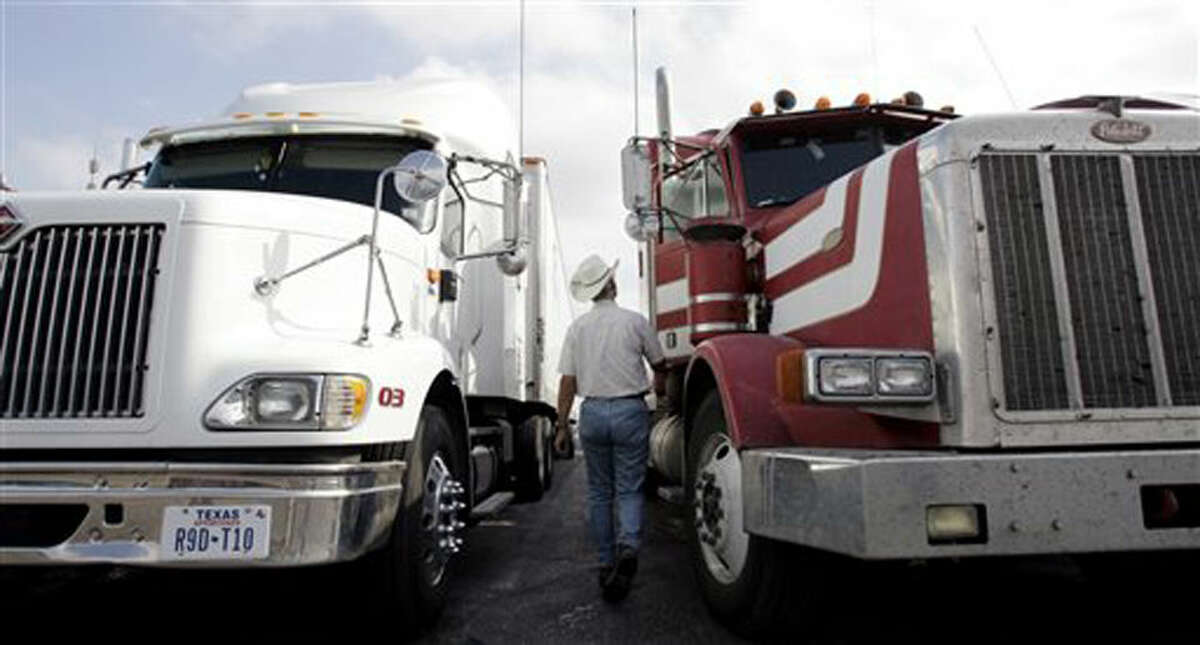FILE - In this Nov. 28, 2006 file photo, a truck driver walks to his truck at a truck stop in San Antonio, Texas. Many tractor-trailers on the nation's roads are driven faster than the 75 mph their tires are designed to handle, a practice that has been linked to wrecks and blowouts but has largely escaped the attention of highway officials. (AP Photo/Eric Gay, File)